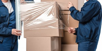 Two,Movers,Wrapping,Cardboard,Boxes,With,Roll,Of,Stretch,Film